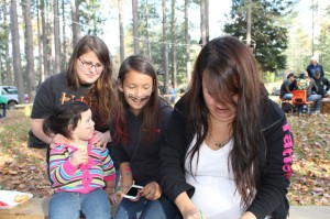 Little Sammarah Francis has her face painted like a kitty cat with Cheyenne & Treasure Paul and Megan Paul, the artist