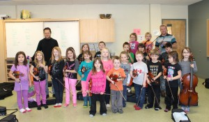 Emmanuel Ortega and Director David Halpine with a class of young musicians in the Sistema Music Program at Mah Sos School at Tobique First Nation