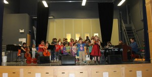 """Music Instructor Emmanuel Ortega plays the piano as the entire student choir performs """"The Green Grass Grew All Around"""""""