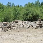 Students have erected two inukshuk in front of a rock wall at the pit
