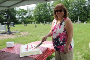 Historical Society President Louise Lennon cuts the celebratory cake