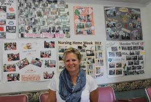 Activities Director Trish St Amand in front of posters documenting and  celebrating the events that have taken place at the Manor