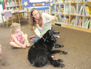 "Angie Hovey reads ""Sun and Moon"" to Mya Williams as  Gidget the Australian Shepard listens approvingly to the story!"